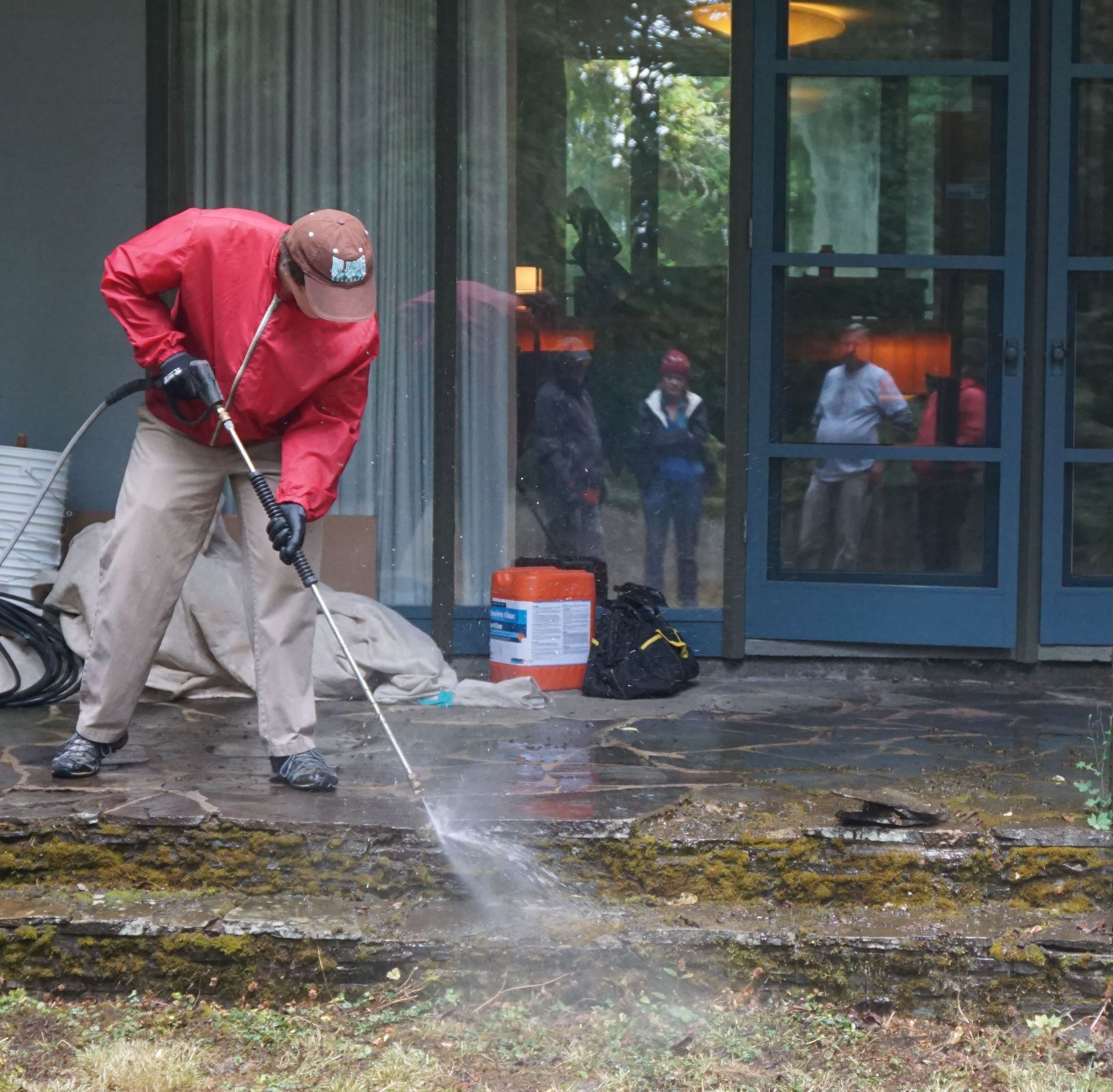 A UO student cleans the back patio stones at the Cottrell house under the watchful eye of the instructors.